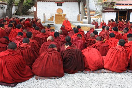 Mediterende monniken bij hun grote leider op de binnenplaats van het Sera klooster-1210
